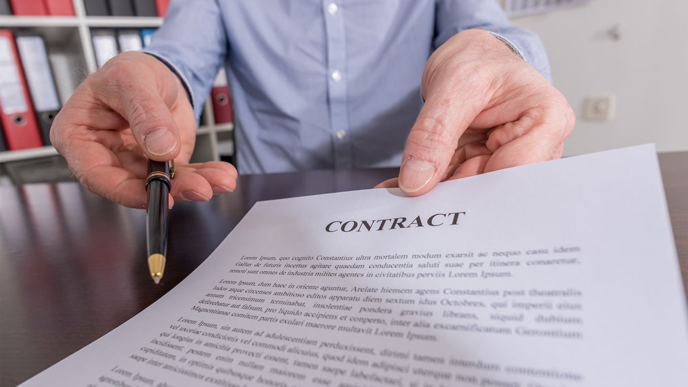 man holding out contract to sign