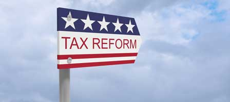 Sign in shape of arrow with Tax Reform written on it. The sign features blue stars and red stripes like a flag.